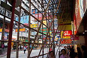 Bamboo scaffolding covers a building in Causeway Bay area of Hong Kong, China. Bamboo scaffolding is still common in China, as a cheaper, and very strong alternative to modern steel poles. They are fixed together using plastic ties. Causeway Bay is a thronging shopping district, with a slightly less western feel than nearby Central.Brightly coloured shop signs hang on the buildings and over the street.