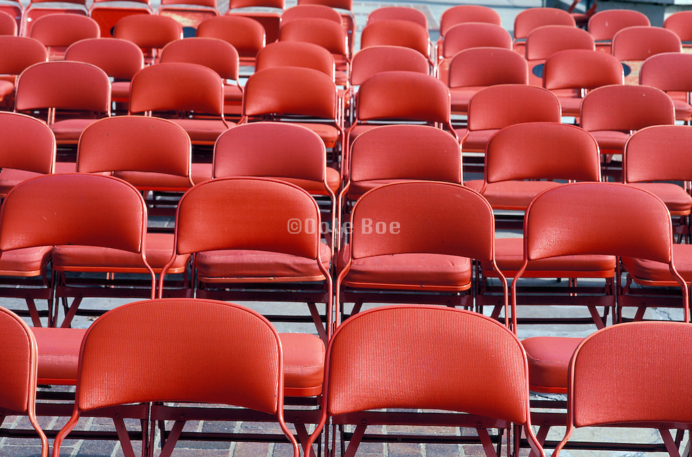 Empty rows of red chairs.