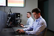 Two men working on computers at a tech company in Denver.