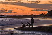 Three people enjoy the sunset on the beach in Laguna Beach, California.