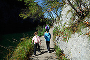Two children (5 years old, 9 years old) walking on path beside lake, Plitvice National Park, Croatia