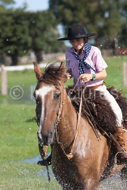 Young boy Gaucho cowboy Brazilian riding a horse through water, close up shot. Working Gaucho Fazenda in Rio Grande do Sul, Brazil.