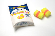 A pair of yellow earplugs and container used to reduce noise including noise caused by snoring
