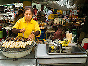 23 DECEMBER 2015 - BANGKOK, THAILAND: A vendor grills bananas in her street stall in the Banglamphu Market. Banglamphu Market (also spelled Bang Lamphu) is close to Bangkok's backpacker haunts of Khao San Road. The market is a popular place for knock off designer clothes and street food. The market is an informal collection of street stalls and sidewalk vendors. Bangkok city officials have plans to evict the vendors, close the market and gentrify the neighborhood. This would follow closing similar markets on Maharat Road and Saphan Lek.       PHOTO BY JACK KURTZ