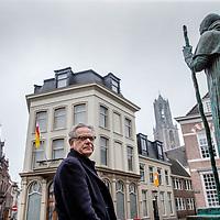 Nederland, Utrecht, 19 februari 2017.<br /> Twan Geurts is schrijver van een boek over de enige Nederlandse paus.<br /> Op de foto: Twan Geurts voor het standbeeld van de Paus voor het Paushuis.<br /> Op de achtergrond de Domtoren.<br /> Twan Geurts (1950) is theoloog en werkt als schrijver en journalist in Utrecht. Eerder publiceerde hij Engelen van deze tijd en Rolduc, dat werd genomineerd voor de M.J. Brusseprijs 2012.<br /> <br /> Foto: Jean-Pierre Jans