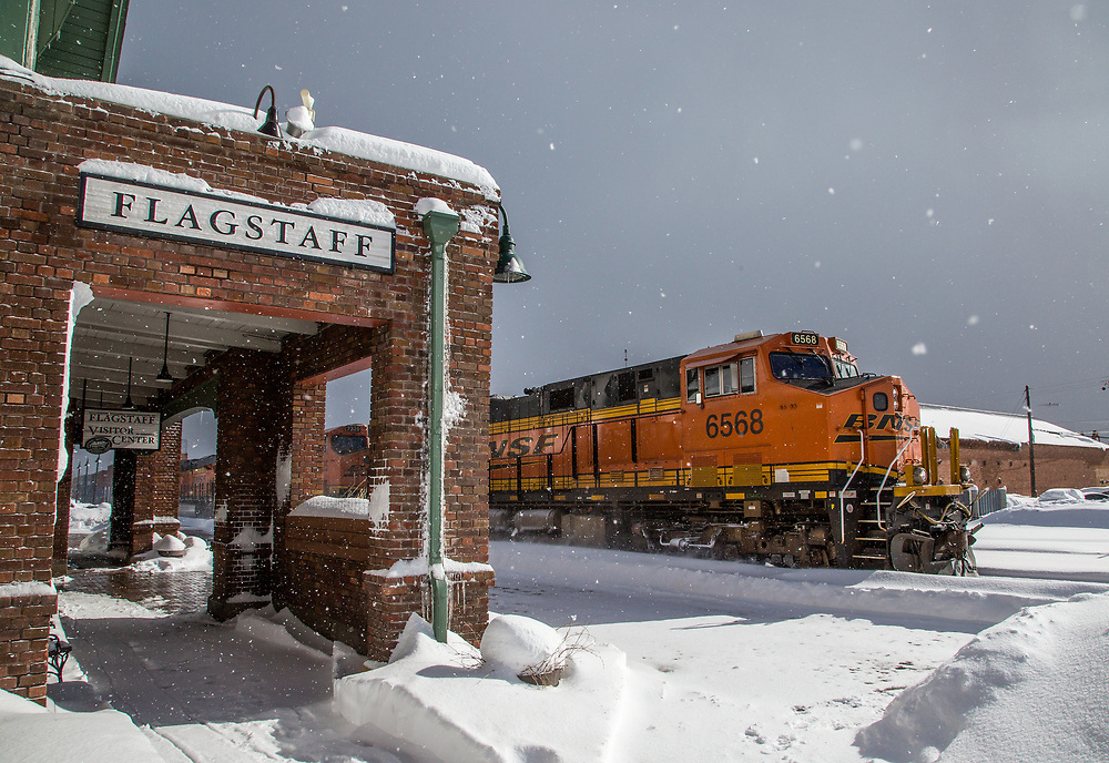 A heavy intermodal train for Oakland, CA plows through the snow as it chugs by the Flagstaff Train Station. Jan 24, 2017.