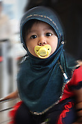 A cute little girl hitches a ride on a cart pushed by her parents at the Kuala Lumpur airport in Malaysia.