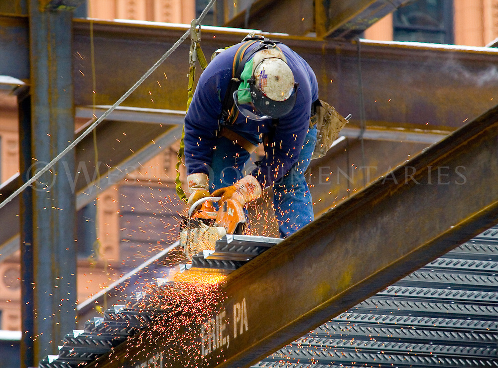 Construction worker, Tony Piscone, from Mckees Rocks Pa., saws off excess sheet metal from the temporary floors at Point Park University's new dance center, which is scheduled to open in the fall of 2007.