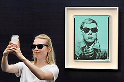 """© Licensed to London News Pictures. 23/06/2017. London, UK. A staf member takes a selfie with """"Self-Portrait"""", 1963-64, by Andy Warhol (estimate GBP5-7m) at the preview of Sotheby's Contemporary Art Sale in New Bond Street.  The auction, which is dominated by Pop art, takes place on 28 June. Photo credit : Stephen Chung/LNP"""