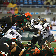 Florida A&M Rattlers quarterback Damien Fleming (11) jumps over defenders to score a touchdown during the Florida Classic NCAA football game between the FAMU Rattlers and the Bethune Cookman Wildcats at the Florida Citrus bowl on Saturday, November 22, 2014 in Orlando, Florida. (AP Photo/Alex Menendez)