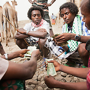 Men are finishing off a deal, buying and selling camels in the Delafagi market. The market is on every Tuesday and people travel from far to sell their goods, to stock up and to socialise.  A strong camel costs 8,000.00 birr( $450.00) and is only bought or sold with the agreement of the entire clan. An AK47 machine gun costs 20,000.00  ($1,100.00) and is shared between the young men of the clan.  Action for Integrated Sustainable Development Association (AISDA) work in the AFAR region of Eastern Ethiopia, based in Delafagi. The Afars practise an old tradition of Female Genital Mutilation where the baby girls has her clitoris and labia cut away and her vagina sewn up. The day before her wedding day the girl is un-stiched ready for marriage. Its a brutal and barbaric tradition which AISDA is challenging with great effect, now more than a hundred girls in Dowe district have been saved from the knife and AISDA is now rolling out the scheme in Delafagi. Delafagi is where the oldest ever human remains have been found, the found is thought to be 4.5 mill years old.
