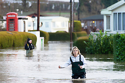 ©Licensed to London News Pictures 21/12/2019. <br /> Yalding ,UK. This lady is walking in the cold flood water with waterproofs on. Little Venice Country Park and Marina in Yalding which has been severely flooded, residents of the lodge and caravan community are having to use boats to get on and off the site. The River Medway in Yalding, Kent has bursts its banks causing severe flooding to the village.   Photo credit: Grant Falvey/LNP