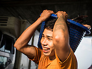 27 OCTOBER 2015 - YANGON, MYANMAR: A porter carries a bucket of fish to a truck in the market at Aungmingalar Jetty in Yangon. The market is home to one of the largest fish markets in Yangon and a meat and produce market.    PHOTO BY JACK KURTZ