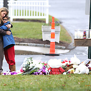 Kady Vales hugs her son Mason, 10, outside the shrine for the victims at St. Rose of Lima Church in Sandy Hook after the mass shootings at Sandy Hook Elementary School, Newtown, Connecticut, USA. 16th December 2012. Photo Tim Clayton