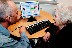 Elderly woman is shown how to use a computer UK