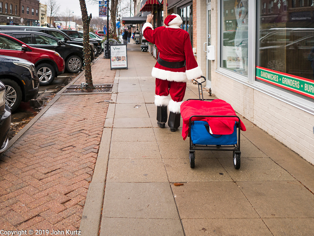 """30 NOVEMBER 2019 - WEST DES MOINES, IOWA: SANTA CLAUS waves while he walks up 5th Street, the main business street in West Des Moines, Saturday. He was handing out gifts to children on Small Business Saturday. """"Small Business Saturday"""" was first observed in the United States on November 27, 2010, as a counterpart to Black Friday and Cyber Monday, which are generally considered events at malls, """"big box"""" stores and e-commerce retailers. Small Business Saturday encourages holiday shoppers to patronize brick and mortar businesses that are small and local. Small Business Saturday is a registered trademark of American Express.      PHOTO BY JACK KURTZ"""