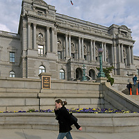 A woman talks on her cell phone as she walks past the U.S. Library of Congress building in Washington, D.C.