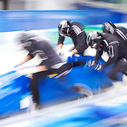 """Winter Olympics, Vancouver, 2010.A German Bobsligh team at the start during the Bobsleigh Four-man competition  at The Whistler Sliding Centre, Whistler, during the Vancouver Winter Olympics. 26th February 2010. Photo Tim Clayton.'BOB'..Images from the Four-man Bobsleigh Competition. Winter Olympics, Vancouver 2010..History was made at the Whistler Sliding Centre when the USA four-man bobsleigh team, led by Steven Holcomb took the Gold. The first time since 1948, a gap of 62 years, since the USA have won an Olympic Bobsleigh gold and they did it with their sleigh named """"Night Train""""...The four days of practice and competition show the tension, nervousness and preparation as the teams of hardened men cope with the challenge of traveling at average speeds of over 150 km an hour. Indeed, five teams had already pulled out of the event before the opening heats because of track complexity, speed and fear, and on the final day, another four teams did not start after six crashes in the first two heats...Teams warm up behind the start complex, warming muscles in the cold in preparation for the explosive start. Many teams prepare in silence, mentally preparing themselves as they wait at the top of the run, in the bobsleigh sheds and the loading areas for their turn. When it's time to slide each team performs it's own starting ritual, followed by the much practiced start out of the blocks for just over four seconds, the teams are then in the hands of the accomplished drivers as they hurtle down the track for just over fifty seconds...Spectators clamber for the best position on track to see the sleighs for a split second, many unsuccessfully try to capture the moments on camera, The rumble of the sleigh is heard then the crowds gasp as it hurtles past in a blur...The American foursome of  Steven Holcomb, Justin Olsen, Steve Mesler and Curtis Tomasevicz finished with a pooled four-heat time of 3min 24.46sec. The German team led by Andre Lange won the Silver Medal in a combined t"""