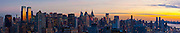 Panoramic photograph of Manhattan looking from high over the Hudson River due south-east, showing the Time Warner Center to the north and Battery Park to the south with the Statue of Liberty framed between Chelsea towers.