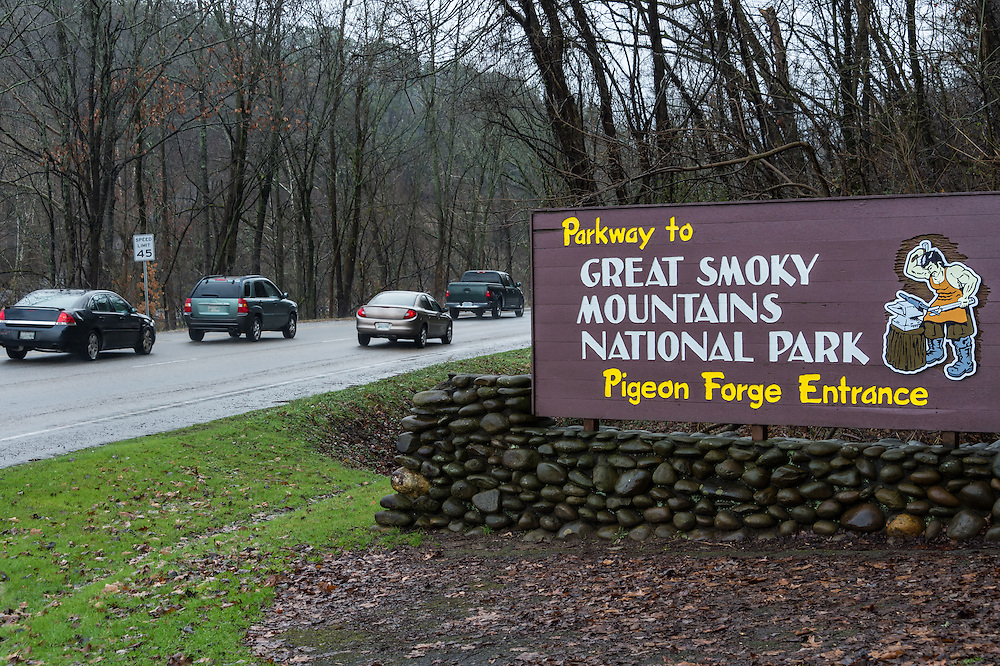 Sign of Pigeon Forge entrance to the Great Smoky Mountains National Park with cars behind