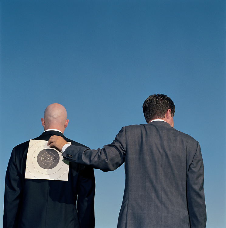 Two businessmen, one putting a target on the other's back, rear view