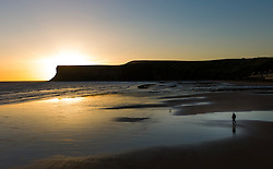 © Licensed to London News Pictures. 14/09/2012..Saltburn, England..A man walks his dog along the beach as the sun begins to rise over Huntcliff in Saltburn, Cleveland..Photo credit : Ian Forsyth/LNP