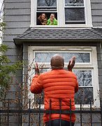 Donald Taylor visits with his daughters, Savannah Quinn, 26, and Frances Rich, 24, and their dog, River, from outside their Humboldt Park apartment while social distancing Sunday, April 12, 2020 during the coronavirus pandemic. (Brian Cassella/Chicago Tribune)