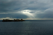 Streamers of sunlight breaking through cloudy sky, Adriatic Sea, near Dubrovnik, Croatia