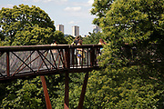 Treetop Walkway at Kew Gardens in London, United Kingdom. The Royal Botanic Gardens, Kew, usually referred to simply as Kew Gardens, are 121 hectares of botanical gardens and glasshouses between Richmond and Kew in southwest London. It is an internationally important botanical research and education institution with 700 staff, receiving around 2 million visitors per year. Its living collections include more than 30,000 different kinds of plants.