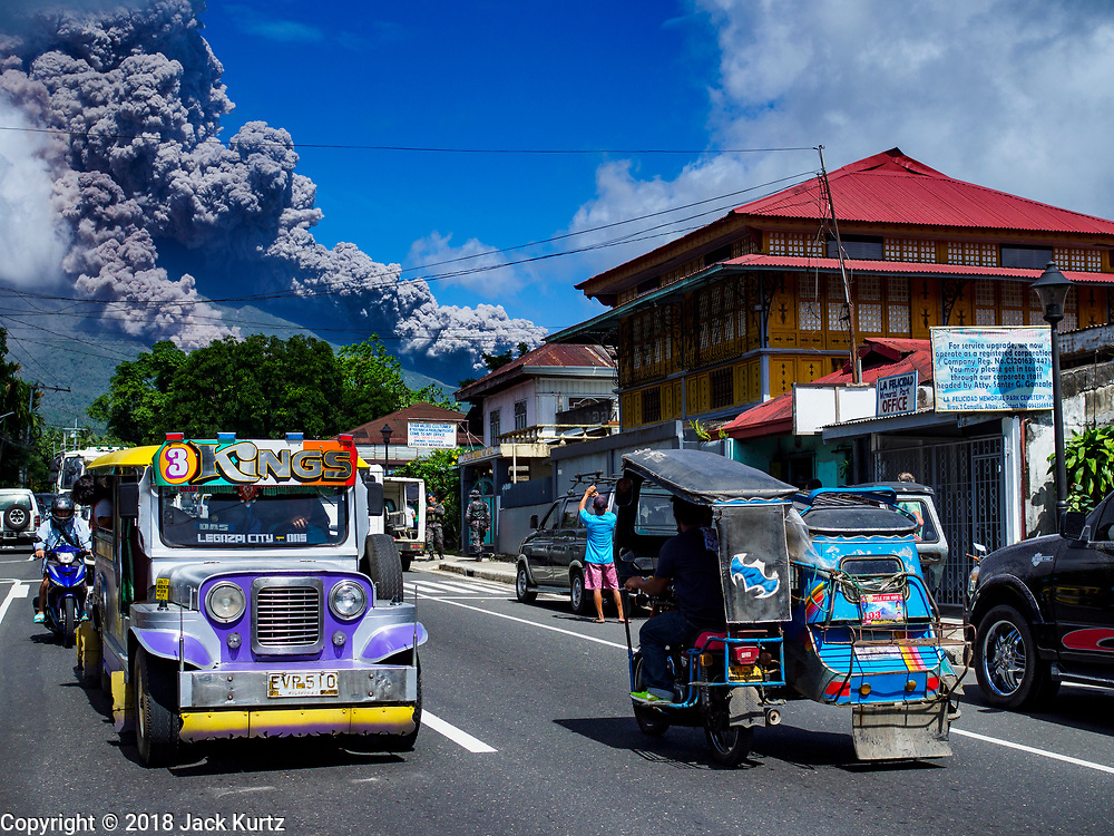 """22 JANUARY 2018 - CAMALIG, ALBAY, PHILIPPINES: An eruption of the Mayon volcano Monday afternoon in Camalig. There were a series of eruptions on the Mayon volcano near Legazpi Monday. The eruptions started Sunday night and continued through the day. At about midday the volcano sent a plume of ash and smoke towering over Camalig, the largest municipality near the volcano. The Philippine Institute of Volcanology and Seismology (PHIVOLCS) extended the six kilometer danger zone to eight kilometers and raised the alert level from three to four. This is the first time the alert level has been at four since 2009. A level four alert means a """"Hazardous Eruption is Imminent"""" and there is """"intense unrest"""" in the volcano. The Mayon volcano is the most active volcano in the Philippines. Sunday and Monday's eruptions caused ash falls in several communities but there were no known injuries.    PHOTO BY JACK KURTZ"""