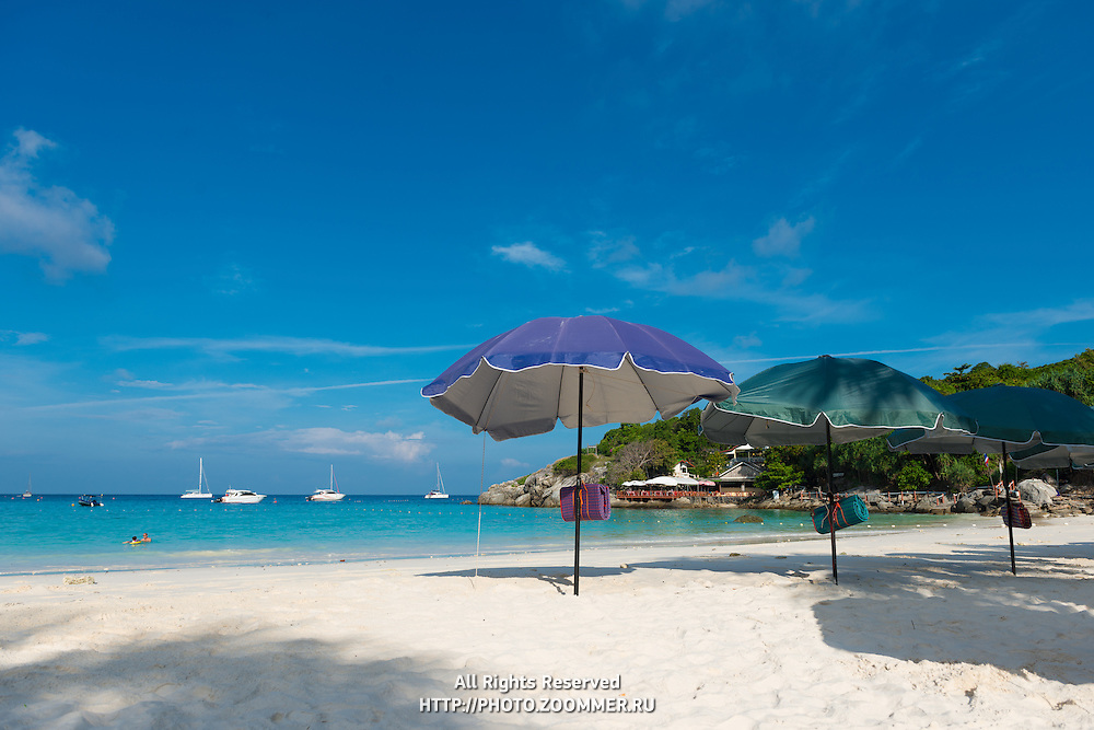 Raya island beach with bright umbrellas parasols