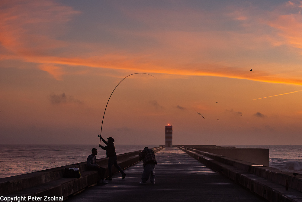 People are fishing on a pier near to the lighting tower in Porto, Portugal
