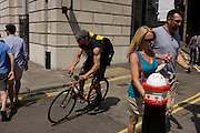 A courier cyclist speeds through a gap between pedestrians in a narrow side street at the junction of King William Street in the City of London, the capital's Square Mile, and its financial heart.