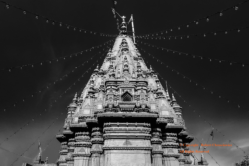Radiating Red Temple (B&W): Radiating Red Temple: Durgakund, the Monkey Temple, is a vibrant red especially when set against a vibrant clear blue sky, while strings of lights radiate from its spire top, Varanasi India.