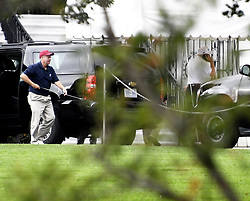 October 14, 2017 - Washington, District of Columbia, United States of America - United States Senator Lindsey Graham (Republican of South Carolina), far left, carries one of his golf clubs as he leaves the presidential limo following a round of golf with US President Donald J. Trump who can be seen at the far right talking on the phone as he enters the White House in Washington, DC on Saturday, October 14, 2017..Credit: Ron Sachs / Pool via CNP (Credit Image: © Ron Sachs/CNP via ZUMA Wire)