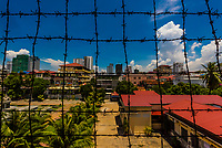 View through barbed wire to the outside world from the Tuol Seng Genocide Museum; originally a school, it was turned into the Khmer Rouge Torture headquarters. Men, women and children were tortured and killed before being moved under darkness to be buried in mass graves at the Killing Fileds of Choeung Ek (outside the city); Phnom Penh, Cambodia.