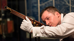 """© Licensed to London News Pictures. 03/11/2016. London, UK.  A staff member shows """"Supreme Number One"""", the first Chinese imperial firearm to be offered at auction, created for the Qianlong Emperor of the Manchu Qing dynasty, est. GBP1-1.5m, at the preview of Chinese artworks entitled """"Treasures Of The Song & Qing Dynasties"""" to be auctioned at Sotheby's in November.   Photo credit : Stephen Chung/LNP"""