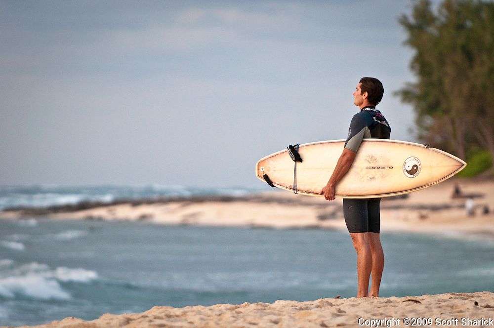 A surfer stands at the shore contemplating the waves.