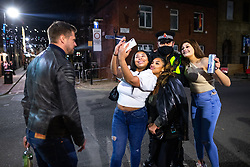 © Licensed to London News Pictures. 12/04/2021. Manchester, UK. A group take a selfie with a police officer on patrol on Canal Street . People on a night out in Manchester City Centre as government restrictions to control the spread of Coronavirus are eased across the UK. Pubs, restaurants, hairdressers, gyms and non essential retailers are now permitted to serve customers within restrictions. Photo credit: Joel Goodman/LNP