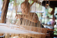 A woman weaves a tapestry in Luang Prabang, Laos.