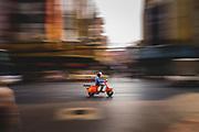 A man driving an orange Vespa motorbike at speed along a street, Chinatown, Bangkok, Thailand