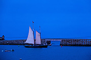 A Windjammer sailboat passes the Bailey Island Bridge, the only granite cribstone bridge in the world, at Orrs Island, Maine. The 1,150-foot bridge crosses Will's Gut and was made using granite slabs as cribstones without mortar or cement. Some 10,000 tons of granite were used in the project.