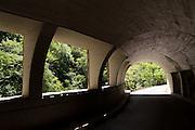 An automobile tunnel leads to the Devil's Bridge (Hudicev most), in Tolmin gorges/Tolminska korita, Triglav National Park, Zatolmin, Slovenia, Europe. Walk a trail along Tolminka river gorge, starting at the parking lot at the Triglavski narodni park (TNP) sign, near Zatolmin in the Julian Alps. Loop upwards to the scenic Devil's Bridge (Hudicev most, built 1907), which carries Tolmin-Cadrg road sixty meters above Tolminka River. Tolmin gorges (Tolminska korita) are among the longest and deepest gorges in Slovenia and are the lowest point (180 meters elevation) in Triglav National Park (TNP).