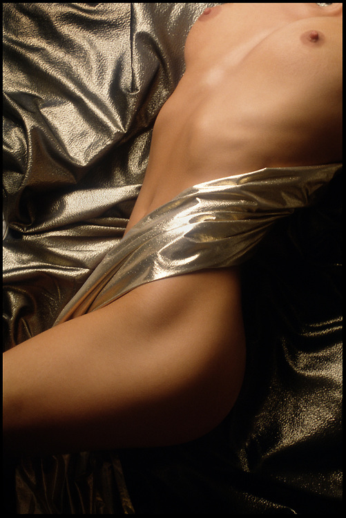Woman's torso wrapped in gold fabric laying on a bed of more gold fabric