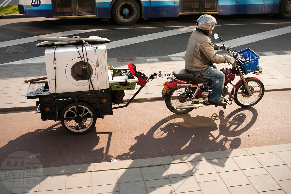 Een man rijdt op een brommer met in de aanhanger allerlei ijzerwaar, waaronder een oude wasmachine.<br /> <br /> A man is transporting garbage on a trailer behind his moped.