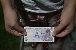 August 16, 2017 - Ankara, Turkey - A 23-year-old unemployment man holds a 5 Turkish Lira banknote in Ankara, Turkey on August 16, 2017. Turkey's youth unemployment rate for people aged 15-24 was 19.8 percent, with a 2.4 percentage point increase in May compared to the same period of 2016. The Turkish Statistical Institute (TurkStat) had reported that the number of jobless people aged 15 and above jumped to 3.2 million in May, marking an increase of 330,000 from the same month last year. (Credit Image: © Altan Gocher/NurPhoto via ZUMA Press)