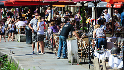People fill the cafes and restaurants beside the harbour in Honfleur, Normandy, france