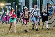 Henham Park, Suffolk, 19 July 2019. The rain arrives but some teenagers dont seem to notice. The 2019 Latitude Festival.