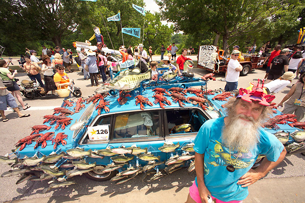 Stock photo of an older bearded man standing beside the fish and lobster car
