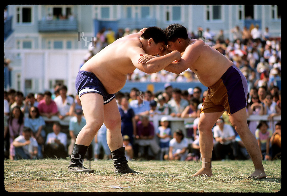 Two men lock heads & arms at a Sakha-style tripping match at the midsummer Ysyakh fest; Yakutsk. Russia